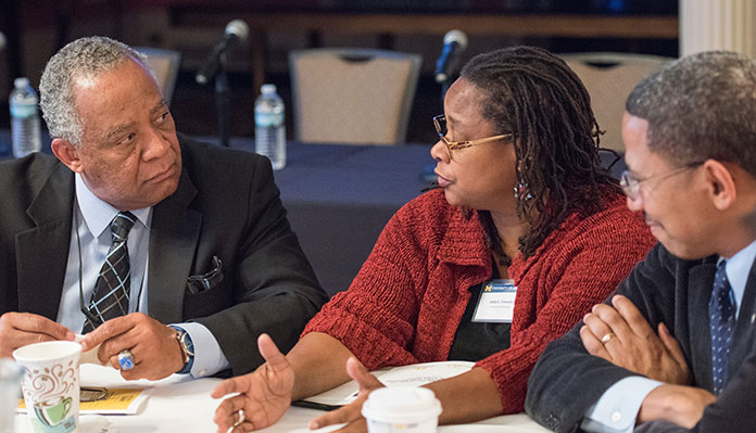 Three people of color siting around a table in discussion at what appears to be a professional conference.